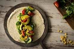 Auf dem Foto ist ein Warp auf einer Pfanne zu sehen. Die Tortilla ist von der Vogelperspektive zu erkennen. In der Mitte der Tortilla ist die Füllung, bestehend aus Salat, Tomaten und gefrorenen Avocadohälften zu sehen. Die Pfanne mit dem Essen drauf, ist auf einem Holztisch zu sehen.
