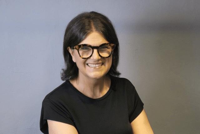 Coco Tan ist die Geschäftsführerin des Unternehmens Greenlife Technologie. Sie sitzt vor einem grauen Hintergrund und trägt ein schwarzes Tshirt. Sie hat schwarze, schulterlange Haare, trägt eine schwarze Brille und lächelt.