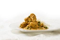 Auf dem hellen Bild ist eine indische warme Mahlzeit auf einem weißen Teller zu sehen. Rechts auf dem Teller befindet sich ein wenig Reis. Die gelbe-Soße mit grünen Erbsen und vielen und großen Stücken zartem Hühnchenfleisch steht im Fokus des Bildes. Der Hintergrund ist weiß.