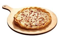 Auf dem Bild erkennt man einen Flammkuchen nach Elsässer Art. Der Flammkuchen ist firsch aufgebacken, welches man an dem goldbraunen Rand und dem geschmolzenem Käse erkennt. Was auf dem Foto klar verdeutlicht wird ist die Zutat der Schinkenstreifen, die den Flammkuchen Elsässer Art aus machen. Der deftige Knusperkuchen liegt auf einem Holzteller.