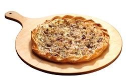 Der Flammkuchen Waldpilze ist mit verschiedenen Arten von Pilzen belegt. Der goldbraun gebrannte Rand verdeutlicht, dass der Flammkuchen eben erst aus dem Ofen gekommen sein muss. Der deftige Knusperkuchen befindet sich auf einem Holzteller.