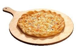 Auf dem Bild ist ein Flammkuchen vier Käse zu sehen. Der Boden ist goldgelb und die vier verschiedenen Käsesorten sind in dem Ofen geschmolzen und goldbraun gebrannt geworden. Der Flammkuchen liegt auf einem Holzteller.