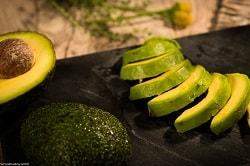 MTG Foodtrading: eine halbierte Avocado ist links im Bild zu sehen, eine Hälfte liegt mit der Schnittseite nach oben, der Kern ist noch in der Avocado. Die zweite Hälfte liegt mit der Schnittseite nach unten. Rechts im Bild ist eine halbe, in streifen aufgeschnittene Avocado zu sehen, ohne Schale.