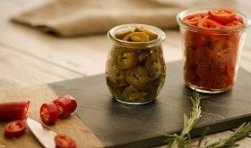 Zwei kleine Gläser nebeneinander stehend , gefüllt mit geschnittenen Chilis. Ein Glas enthält grüne, das andere rote Chilis. Links daneben ist eine angeschnittene rote Chili zu sehen. Messer und Abschnitt liegen neben der geschnittenen Chili.