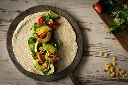 Ein belegter, ungerollter Tortilla Wrap liegt auf einem nur etwas größerem, auch runden donkel braunem Holzbrett. in der Mitte des Wraps liegen große Avocado Stücke, Feldsalat, Mais und Tomatenstücke.