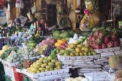 Obst und Gemüsestand in Südostasien. Gestapelte Papaya, Mango, Granatäpfel uvm Früchte in Holzschiffchen.