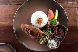 Auf dem Foto ist ein brauner Teller mit Reis, einem Hühnchenschnekel und Beilagen zu sehen. Rechts von dem Reis sind Früchte, die zur Dekoration dienen. Dadrunter ist ein grüner Salat aus einem Gemüse, welches aussieht wie eine Zucchini. Rechts unten auf dem Teller sind zwei kleine runde Schalen. Die Obere ist mit einem rot-braunen Dip gefüllt und die untere mit weißem Krautsalat.