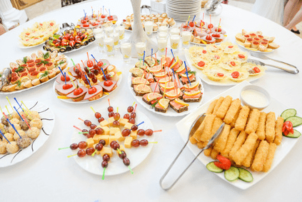 Auf dem Tisch sind mehrere Teller mit Snacks und kleinen Häppchen gedeckt. Links befinden sich auf dem weißen Teller Spieße mit Käse und Weintrauben. Rechts davon erkennt man Fischstäbchen, die mit einer Zange, die an der linken Ecke des eckigen Tellers ist, vom Gast genommen werden sollen. Außerdem erkennt man dahinter mehrere Variationen von Butterbroten, mit Wurst oder Käse belegt und mit Obst verziert. In den Broten, ebenso wie in den Schokoladen- und Vanillebällchen links, stecken kleine Spieße zum aufgreifen der Snacks. In der MItte des Tisches ist ein weißes Standbein zu sehen, möglicherweise das eines Kerzenständers. Um dieses Bein herum sind Kurzegläser gefüllt mit einer Art Pudding oder Creme, die den Nachtisch und die süße Versuchung darstellen soll.