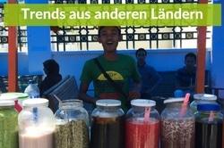 Ein Stand in Südostasien mit einem Lachenden Vekaäufer hinter einem kleinen per Hand ziehbaren Waagen auf dem im Vorfergrund in großen Gläsern Suppen und Gemüse, Toppings sind.