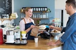 Auf dem Bild ist die Theke eines Coffeeshops abgebildet. Die Verkäuferin hat in der rechten Hand das Produkt, welches der Kunde gerade gekauft hat, in einer braunen to-go Tüte in der Hand. Mit der anderen Hand reicht sie ihm seine EC-Karte, mit der der Kunde, der vor der Theke in einem blauen Shirt steht, bezahlt hat. Die Verkäuferin hat die blonden Haare zu einem Pferdeschwanz, trägt eine rosa Blus und eine dunkelblaue Schürze. Die Theke vor ihr ist aus Holz. Im Hintergrund sind Regale zu erkennen und die Wandfarbe des Coffeeshops ist blau.