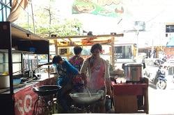 Auf dem Foto erkennt man einen Stand in Asien, an dem eine Frau und zwei Männer kochen. Die Frau, die zur Kamera gewandt ist,. trägt über dem weißen Langarm-Shirt eine rosa Schürze und kocht im Wok. Neben ihr ist ein Junge in einem blauen Shirt. Vor ihm steht ebenfalls ein Wok, der aber nicht benutzt wird. Dahinter ist der Stand zur Straße, an dem ein anderer Junge steht um für die Leute zu holen. Rechts auf dem Bild erkennt man einen Tisch auf dem ein Reiskocher steht.