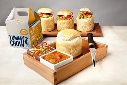 Auf dem Bild ist das Produkt von Andre Fordyce zu sehen. Im Vordergrund ist ein Tablett,welches schräg steht. In der hinteren rechten Ecke ist das Brötchen zu sehen, rechts daneben an der Ecke ein Messer zum Aufschneiden des Brötchens. Links auf dem Tablett sind zwei Schalen mit Soßen. Das obere, durchsichtige Schälchen beinhaltet eine Art Salatmix aus Paprika, Lauch etc. Die weiße Schale daneben beinhaltet eine orangene Soße mit Gemüse und Fleiisch. Im Hintegrrund steht ein längliches Tablett, welches aufzeigt wie das Brötchen gefüllt aussieht. Die obere Klappe der Brötchen ist abgeschnitten, der Inhalt der Schalen wurde hineingepackt und die zuvor abgeschnittene Seite wieder aufgesetzt. Zwischen den beiden Tabletts steht links eine Verpackung, die mit dem Produktnamen beschriftet ist und die farben grau und orange hat. Das ist die to-go Verpackung des Yummy Chows.