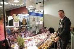 Ein Standmitarbeiter auf der Messe zeigt die Snack-Trends 2017 auch für Hotellerie und Hotelgastronomie.