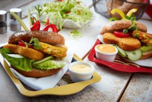 Auf dem Bild sind zwei Burger mit dem Gemüse Schnitzel von Avita drauf. Avita ist die vegetarische und vegane Marke von Schne-frost. Die dunklen Burger-Buns sind mit den Gemüse-Schnitzeln, Salat, Gurken und Soße belegt. Serviert werden Sie auf einem jeweils roten und gelben länglichen Tablett. Dazu wird eine Soße in einem weißen Schälchen gereicht. Im Hintergrund befindet sich Salat und Pfeffer und Salz.