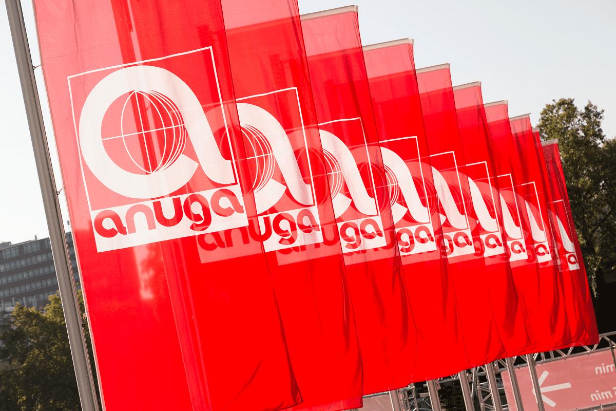 Auf dem Foto sind mehrere rote Fahnen hintereinander zu erkennen, die das Logo der Branchenfachmesse Anuga haben.