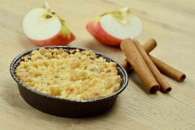 Auf dem Foto ist der Apple Crumble von der Biebelhausener Mühle abgebildet. Dabei handelt es sich um einen Apfelkuchen mit Streusel, der in einer schwarze Schale geliefert und gebacken wird. Um den Kuchen liegen noch Zimtstangen und zwei Apfelstücke zur Dekoration.