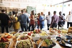 Im Fokus des Bildes ist der Tisch mit verschiedenen asiatischen Gerichten zu sehen. In unterschiedlichen runden und quadratischen Schüsseln befinden sich unter anderem Nudeln, Soßen aber auch Snacks und dazugehörige Dips. Im Hintergrund erkennt man unscharf viele Leute. Man könnte vermuten, dass dieses Buffet bei einer Betriebsfeier in der Betriebskantine statt findet.