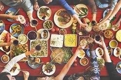 Das Foto ist aus der Vogelperspektive gemacht, deshalb blickt der Zuschauer auf den Tisch herab. Man erkennt einen Tisch, der mit einer roten Decke bedeckt ist und mit unterschiedlichen asiatischen Gerichten gedeckt ist. Die Gericht befinden sich in runden und quadratischen Schüsseln. Unter anderem sind Nudeln zu sehen, Curry, aber auch Gemüse. Man erkennt Hände und Arme die über den Tisch greifen, jedoch sieht man nicht die Körper oder Köpfe der Personen, die essen.