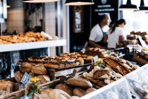 Backwaren_auf dem Bild ist eine Backwarenauslage einer Bäckerei zu sehen. Vorne liegen Brote und weiter hinten süßes Gebäck.
