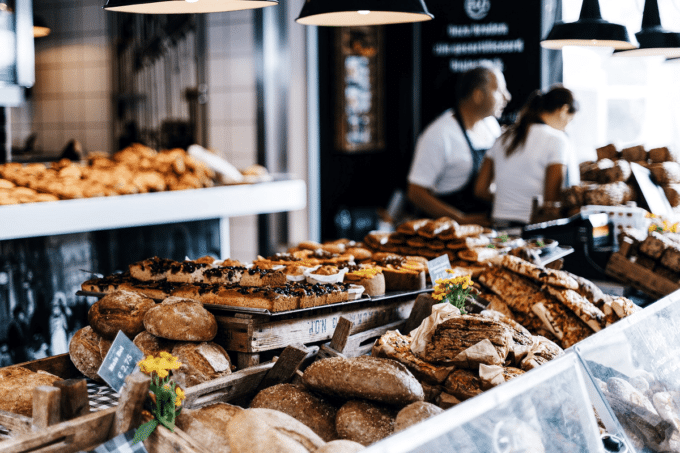 Auf dem Bild erkennt man eine Auslage bei der Bäckerei. Vorne im Fokus sind Backwaren aller Art zu sehen: Brötchen, Brot, Brotstangen und Kuchen. Über der fokussierten Theke hängen schwarze Lampen, die angeschaltet sind. Im Hintergrund erkennt man, dass die Bäckerei in schwarz-weiß gehalten ist. Man erkennt den Laden und ganz hinten sogar zwei Mitarbeiter in weißem T-Shirt und schwarzer Schürze.