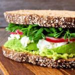 belegtes Vollkornbrot mit Salat, Radieschen und Avocadocreme