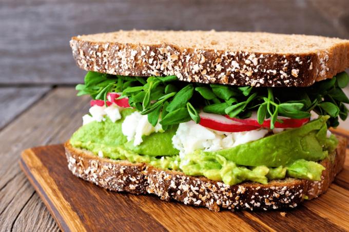 Ein Sandwich belegt mit Salat, Radieschen und Avocadocreme