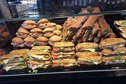 Auf dem Foto erkennt man eine Auslage in einer Bäckerei. Es sind viele belegte Backwaren zu sehen, die zum Teil sogar übereinander gestapelt werden. Vorne in der Vitrine sind Baguettes, dahinter auf der linken Seite belegte Brötchen und neben den Brötchen sind lange und große Baguettes zu sehen.