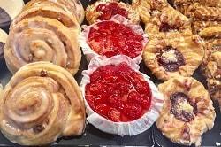 Auf dem Bild erkennt man eine Auslage in der Bäckerei mit süßen Backwaren. Ganz links ist eine Reihe Vanille-Schnecken mit Rosinen. In der Mitte befinden sich drei Himbeer-Törtchen und ganz rechts ist eine süße Backware, die in der Mitte mit Früchten gefüllt ist. Alle drei Sorten sind rund.