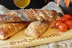 Auf dem Foto erkennt man ein Holzbrett mit drei übereinander liegenden Brotstangen. Die oberste Brotstange, die quer auf zwei anderen liegt, ist mit Mohn umhüllt. Die beiden unteren Stangen sind ebenfalls mit weiteren Zutaten versehen. Die linke Stange scheint mit Käse überbacken worden zu sein und die rechts ist mit weiteren Körnern versehen. Links auf dem Brett von den Stangen liegen Tomaten. Im Hintergrund erkennt man ein halbes Glas mit Bier. Das Holzbrett ist auf einer grauen Tischdecke auf einem Tisch.