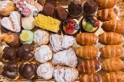 Das Foto ist aus der Vogelperspektive geschossen. Man erkennt von oben eine Auswahl an süßen Backwaren. Links sind Croissants zu sehen in zwei Reihen. Daneben sind gefüllte Plundertaschen, die mit Puderzucker versehen sind. Ganz links sind gefüllte Backwaren, die mit Schokolade überzogen sind. Oberhalb dieser Reihen sind weitere Cupcakes, Kuchen, Plundertaschen und Schokoladenkuchen.