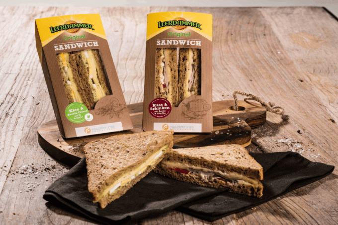 Auf dem Foto erkennt man die beiden neuen Sorten vom Leerdammer Original Sandwich in einer praktischen dreieckigen to-go-Verpackung. Rechts ist das Sandwich belegt mit dem Leerdammer Käse von Bel zu sehen und Schinken, links ist das Vollkornbrot nur mit Käse und einer Rucolacreme belegt bzw. bestrichen. Die Verpackung ist braun, da sie aus Pappe ist und hat am Kopfanfang des Sandwiches den typscih gelben Rand mit der Aufschrift Leerdammer drauf.