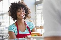 Eine Frau lächelt über dem Tresen auf diesem Foto. Sie ist die Bedienung in einem Coffeeshop, denn sie trägt eine rote Schürze und bedient die Person, von der man unscharf am rechten Rand des Bildes einen Arm und ein weißes T-Shirt sieht. Unter der Schürze trägt die Frau ein blua-weiß gestreiftes T-Shirt mit V-Ausschnitt. Sie hat kurze braune und sehr lockige Haare. Im Hintergrund erkennt man unscharf den Rest des Coffeshops durch kleine Regale.