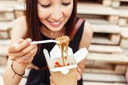 Auf dem Foto ist eine junge Frau zu sehen, die eine Asia-Nudel-Box in der Hand hat. Sie isst die NUdeln mit einer Gabel und schaut auf sie hinunter. Die Box ist hellbraun und innen weiß. Die Frau hat rote Haare und trägt ein schwarzes T-Shirt. In Hintergrund erkennt man, dass sie auf Holztreppen sitzt.