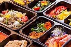 Auf dem Foto erkennt man kleine Portionsmengen, die in einen schwarzen Doppelbehälter aus Plastik abgepackt sind. Es befinden sich unterschiedliche Gerichte und Zutaten in den Behältern.