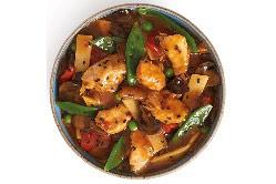 Auf dem Bild ist eine Schüssel mit dem aus China inspiriertem Gericht des Peking Hühnchens vom belgischen Hersteller Delasia. Aus der Vogelperspektive ist Hühnchen, Sprossen, Erbsen und weitere Gemüsearten in einer rot-braunen Soße zu erkennen.