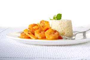 Das rote Scampi Curry von Delasia, vom Hersteller Food Impact, ist mit einer Portion Reis auf einem weißen Teller in einer hellen weißen Umgebung platziert. Auf dem Reis liegt Minze oder Basilikum zur Dekoration. Man erkennt klar und deutlich die große Garnelen in der roten Currysoße.