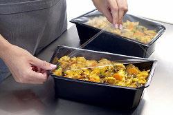 In dem Bild ist das asiatische Gericht in einem schwarzen Container zu sehen. Während im Hintergrund eine Hälfte bereits fertig laminiert wurde, wird die im Fokus stehende Hälfte der beiden Container gerade von einer Arbeitskraft mit durchsischtiger Folie verschlossen.