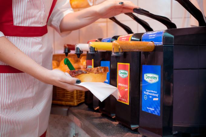 Auf dem Foto erkennt man mehrere Senf-Spender, die mit den Senfsaucen von Develey befüllt sind. Eine Person in einer weißen Schürze, benutzt einen der vier Saucenspender für eine Wurst, die sie dadrunter hält. Die Saucen-Spender haben verschiedenen Farben, sodass man unterscheiden kann wo welche Sauce bzw. welcher Senf drin ist.