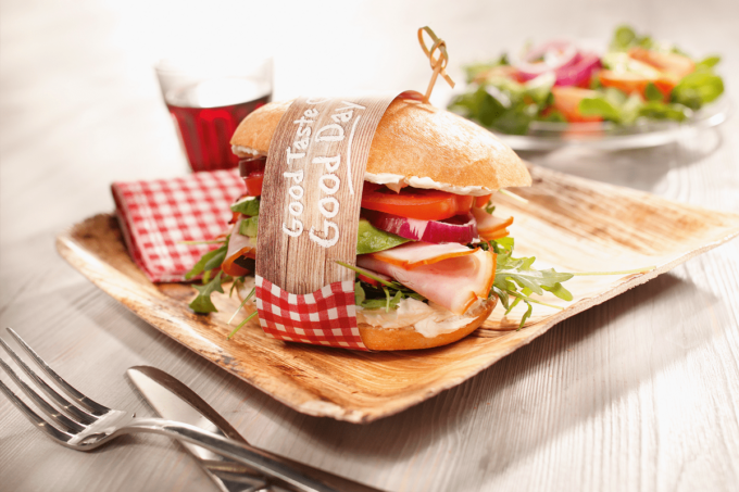Der Gourmet Burger von Edna ist fix und fertiig mit den neuen Edna-Brötchen. Dieser Burger ist mit Schinken, Salat, Tomaten belegt und hat ein Band quer um den Burger herum. Er befindet sich auf einem Holzbrett.