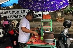 Auf dem Foto erkennt man einen Mann,der einen Stand besitzt an dem er Essen auf der Straße kocht - Streetfood. Der kleine Wagen in grün und auf ihm befindet sich ein Reiskocher und ein paar Kochutensilien. Der Wagen ist so abgelichtet, dass man ihn von der Seite erkennt. Am hinteren Teil des Wagens ist ein Sonnenschirm in lila mit weißem Muster befestigt, um den Koch, also den mann im weißen T-Shirt und schwarzer Cap, der hinter dem Wagen steht, vor der Sonne zu schützen. Hinter dem Mann und auch vor dem Stand befinden sich Roller, an denen jeweils links oder rechts ein Helm hängt. Im Hintergrund ist eine Art Sitzmöglichkeit aus Holt und an der dahinter gelegenen Wand ist ein weißes Schild zu sehen auf dem in schwarzen Buchstaben etwas auf indonesisch geschrieben steht.