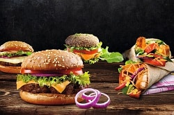 Auf dem Foto erkennt man drei Burger und zwei Wraps. Die Burger sind belegte mit einem Patty, Salat, Tomate, Zwiebeln und vor allem dem neuen würzigem Käse von Frischpack. Im Vordergrund ist ein Burger zu erkennen, und hinter diesem sind links und rechts jeweils auch einer. Rechts vor dem ersten Burger sind zwei Zwiebelringe. Rechts von den Burgern befinden sich die zwei Wraps, die quer übereinander liegen. Die Wraps sind ebenfalls mit Salat, Tomaten, Zwiebeln und dem Käse von Frischpack gefüllt. Alle fünf Produkte sind auf einem Holztisch vor einerm schwarzen Hintergrund abgebildet.