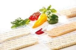 Auf dem Foto ist die verschiedene Auswahl des würzigen und neuen Käses von Frischpack zu sehen. Es liegen jeweils zwei abgepackte Käsepackungen nebeneinander zw. sich versetzt gegenüber. Auf dem weißen Tisch ist hinter den Käseverpackungen ebenfalls noch Gemüse abgebildet. Unter anderem: Grüne Paprika, gelbe Paprika, zwei Chilischoten, Salat und kleine Cherrytomaten