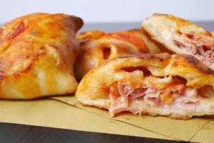 Es ist ein Käse-Schinken-Snack abgebildet. Der Käse ist in der Backwaren während des Aufwärmens oder Grillens geschmolzen. Man erkennt den Snack sowohl aufgeschnitten von der Seite, als auch als Ganzes. Mehrer solcher Schinken-Käse-Snacks liegen nämlich auf einem Holzbrett.