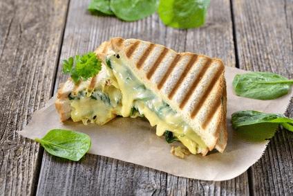 Auf einem Pergamentpapier ist ein heißes, gegrilltes Sandwich zu erkennen. Der Snack ist mit Spinat und Käse belegt. Durch das Grillen ist der Käse geschmolzen und das Sandwich hat Grillstreifen bekommen.
