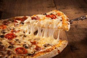 Eine Pizza belegt mit Käse, Salami, Tomaten und Pilzen, dessen Käse zerläuft