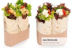 """Auf dem Foto sind die Wraps """"Meisterrolle"""" von Jouis Nour zu sehen. Man erkennt den Inhalt des Wraps, da der obere Teil hinausschaut. Im linken Wrap befindet sich Salat, Tomate und Curry-Hühnchen. Rechts beinhaltet der Wrap Salat, Tomate und Feta. Beide Wraps sind aus Bio-Herstellung und befinden sich jeweils zu zweit in einer braunen Verpackung aus nachhaltigem Papier."""