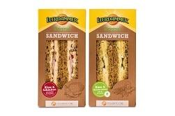 Auf dem Foto erkennt man die beiden neuen Sorten vom Leerdammer Original Sandwich in einer praktischen dreieckigen to-go-Verpackung. Rechts ist das Sandwich belegt mit dem Leerdammer Käse von Bel zu sehen und Schinken, links ist das Vollkornbrot nur mit Käse und einer Rucolacreme belegt bzw. bestrichen. Die Verpackung ist braun, da sie aus Pappe ist und hat am Kopfanfang des Sandwiches den typscih gelben Rand mit der Aufschrift Leerdammer drauf. Die beiden verpackten Sandwiches befinden sich auf einem Schneidebrett auf einem Holzfußboden. Vor ihnen ist jeweils ein Sandwich jeder Sorte auf einem schwarzen Tuch hingelegt worden.