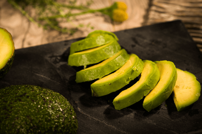 Durch die schwarze Farbe des Teller, kommt die grüne Außen- und gelbe Innenfarbe der Avocadostücke besonders zu Geltung. Die gefrorenen Avocado Slices sind mit der grünen Seite zum Zuschauer gewandt, angerichtet. Unten links sieht man noch eine ganz Avocado mit Schale und Kern.