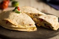 Auf dem Foto erkennt man eine Quesadilla. Es sind mehrere Tortillas von MTG Foodtrading gestapelt. Zwischen den Tortillas befinden sich Zutaten wie Käse, Fleisch,Mais und weitere Zutaten, die jedoch für den Zuschauer schwer zu identifizieren sind. Auf der Quesadilla liegt zur Dekoration eine kleine Tomate und ein paar Kräuter. Das Gericht befindet sich auf einem runden Holzbrett auf einem hell-braunen Holztisch. Im Hintergrund erkennt man verschwommen weitere Tomaten in grün und rot und eine blaue Serviette.