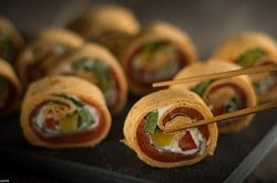 Auf dem Foto erkennt man Sushi. Jedoch ist es kein typisches Sushi, denn die Algenblätter, die normalerweise außerhalb der Shushirolle sind, sind aus der Tortilla von MTG Foodtrading. Das Sushi steht seitlich zur Kamera, sodass man die Füllung, die aus Lachs, roter und gelber Paprika und Sour Cream besteht, erkennen kann. Der Fokus liegt dabei auf der vordersten Sushirolle, doe auch von zwei Essstäbchen kurz davor ist aufgenommen zu werden. Im hintergrund sind die anderen Tortilla-Sushi-Rollen verschwommen zu erkennen. Die Rollen sind auf einem schwarzen Tablett serviert.